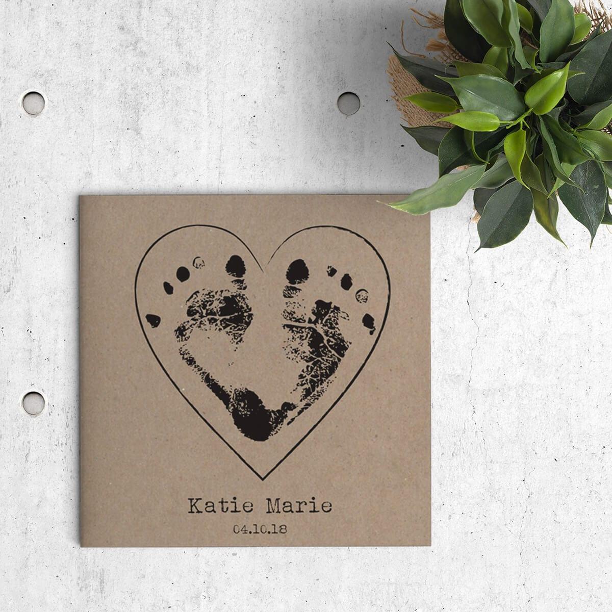 Geboortekaartje Voetafdrukjes op Kraft is een ontwerp gedrukt op kraftpapier, waarbij op de voorkant 2 voetafdrukjes van een baby een hartje vormen. Voorzijde van kaartje.