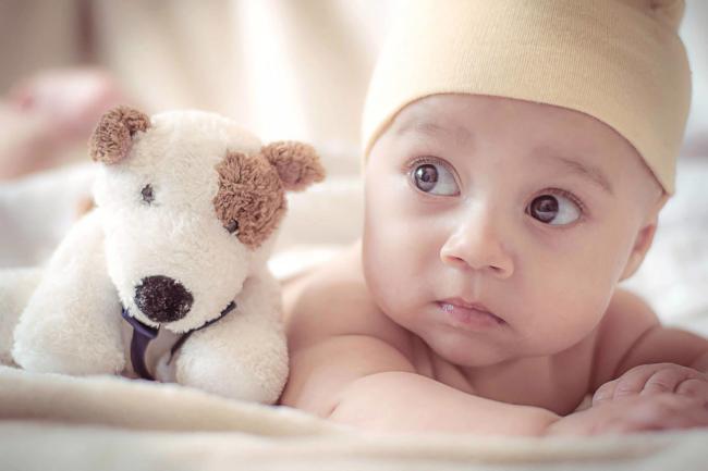 Kleine baby met knuffel   Wanneer geboortekaartjes versturen? Etiquette vraag.