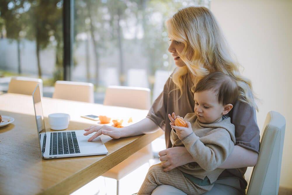 Vrouw met baby op schoot achter laptop geboortekaartjes aan het bestellen